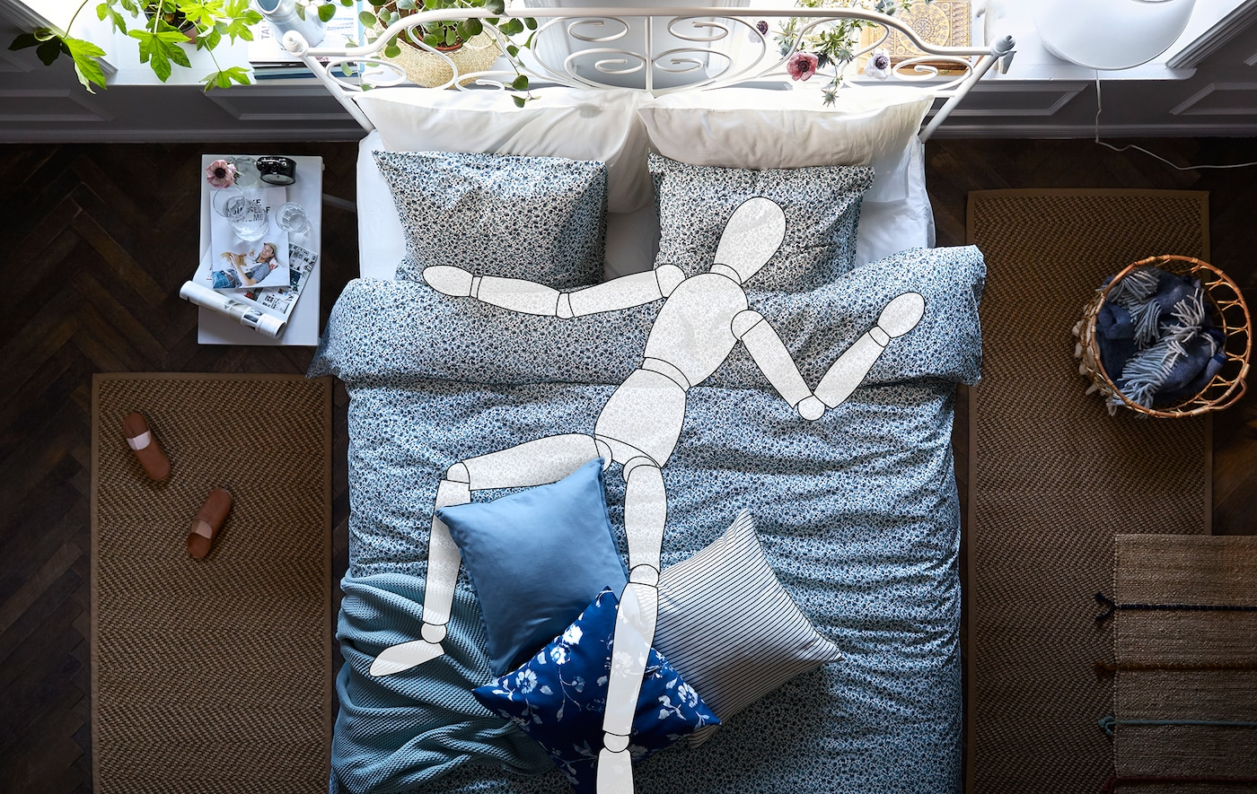 ديكور غرفة نوم داخلي بسرير عريض. الخطوط العريضة لدمية فنان بحجم إنسان طبيعي ممتدة أعلاه.