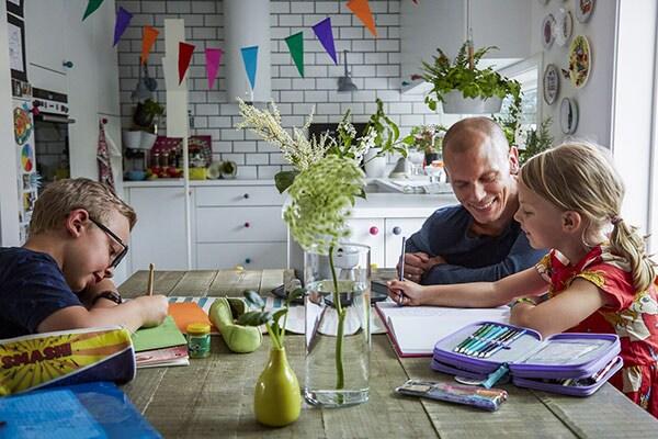 dzieci z tatą uczą się przy stole