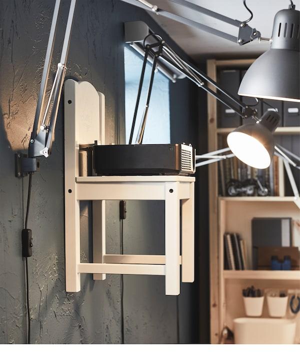 Dziecięce krzesło zawieszone na haczykach ściennych. Krzesło, otoczone przymocowanymi do ściany lampami biurkowymi, służy do przechowywania projektora filmowego.