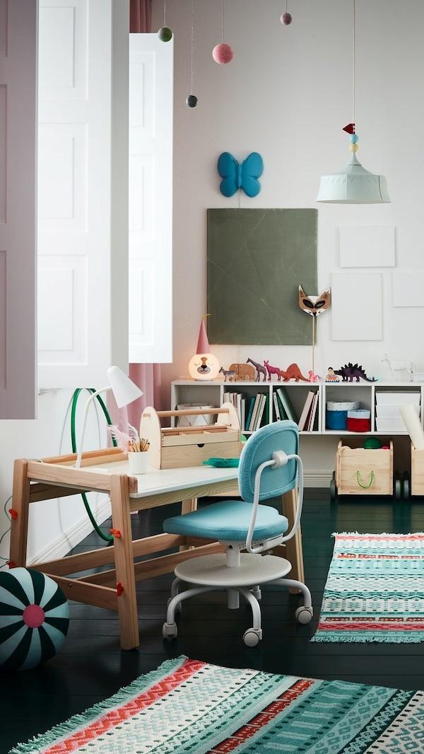 Dziecięcy pokój z kolorowymi dywanami, turkusową ramą łóżka, białą szafą, różowymi zasłonami i dziecięcym biurkiem.