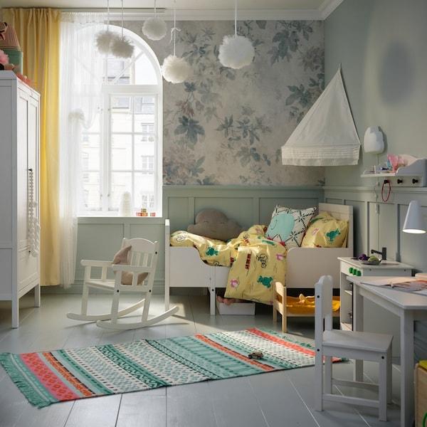 Dziecięcy pokój z łóżkiem, baldachimem, szafą, stołem i krzesłem w kolorze białym. Kolorowy dywan pośrodku pokoju.