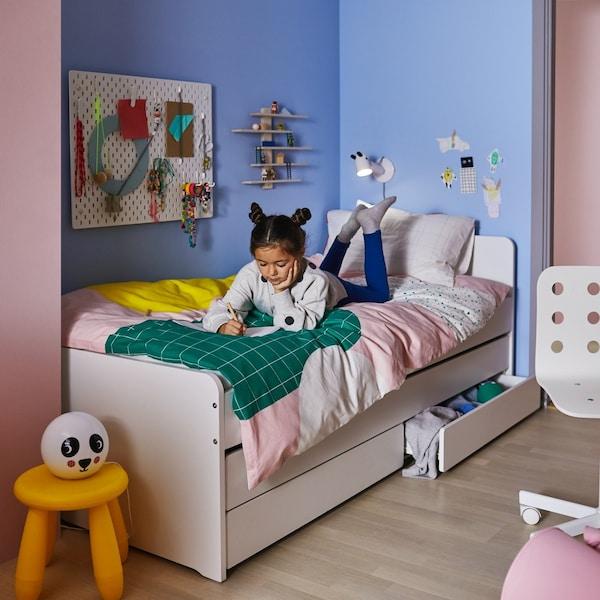 Dziewczyna leżąca na łóżku SLÄKT i czytająca książkę.