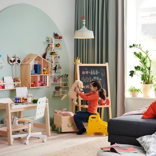 Dziewczynka bawiąca się pluszakiem w swoim pokoju. Na suficie wisi lampa TROLLBO.