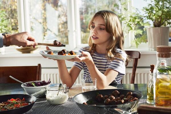 Dziewczynka siedząca przy stole w jadalni trzyma talerz, na który nakładane są klopsiki wegańskie ALLEMANSRÄTTEN.