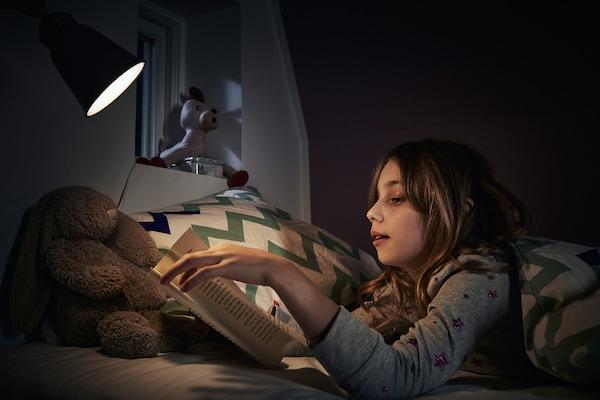 Dziewczynka w piżamie leży wieczorem w łóżku i czyta książkę przy lampce nocnej.