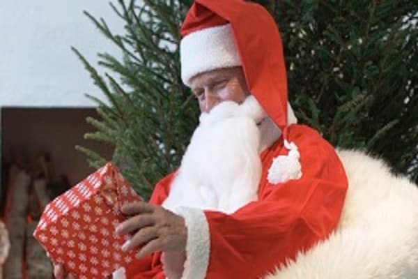 Santa Claus sitting in a fuzzy chair holding a present.