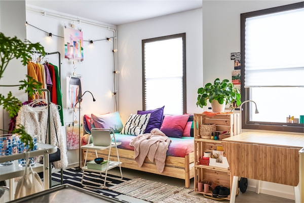 Densely furnished small-space apartment with shelf, clothes rack and a sofa made by cushions and a two low, stacked beds.