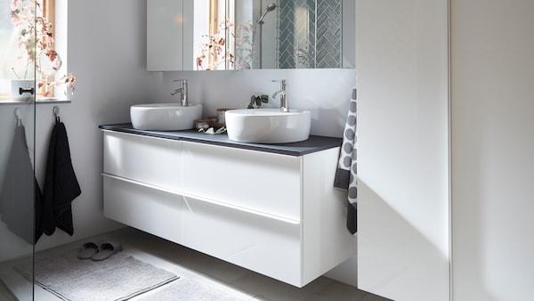 Umyvadlová skříňka se dvěma umyvadly a zrcadlovými skříňkami.