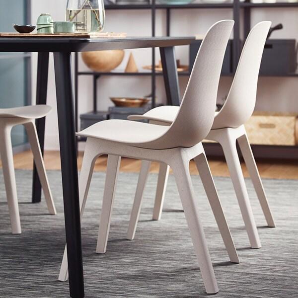 Odger stole i en lys farve står rundt om et mørkt bord i en stuen