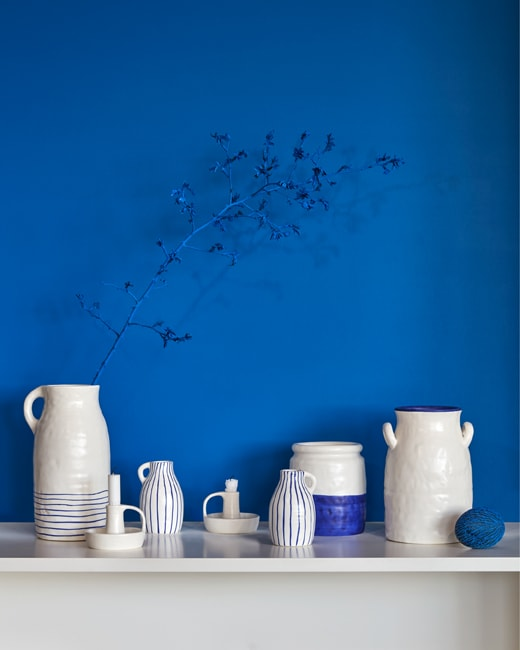 A blue wall with a white table top covered in blue and white ceramic vases.