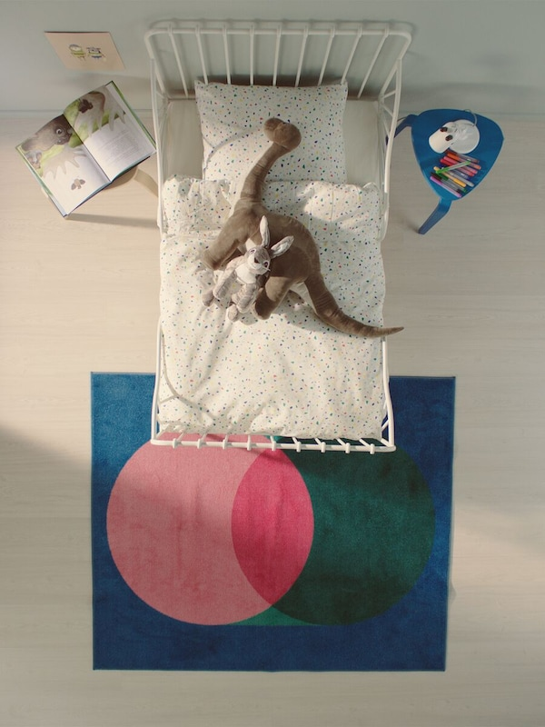 Bird's eye view of a white metal kids bed with a dinosaur and rabbit soft toy, and a blue rug with pink and green circles.