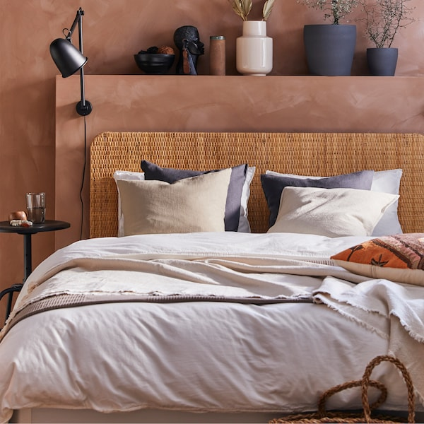 Bedroom with a bed with rattan headboard, dark grey plant pots, black wall lamp, white bed textiles and beige cushion covers.