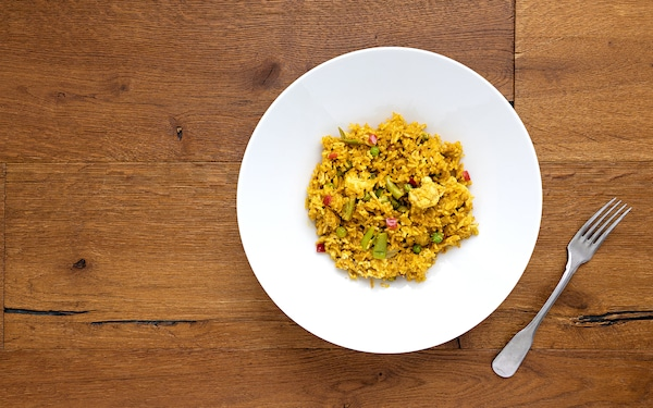 Vegetable biryani with chunky cauliflower, red peppers and green beans on a wooden table