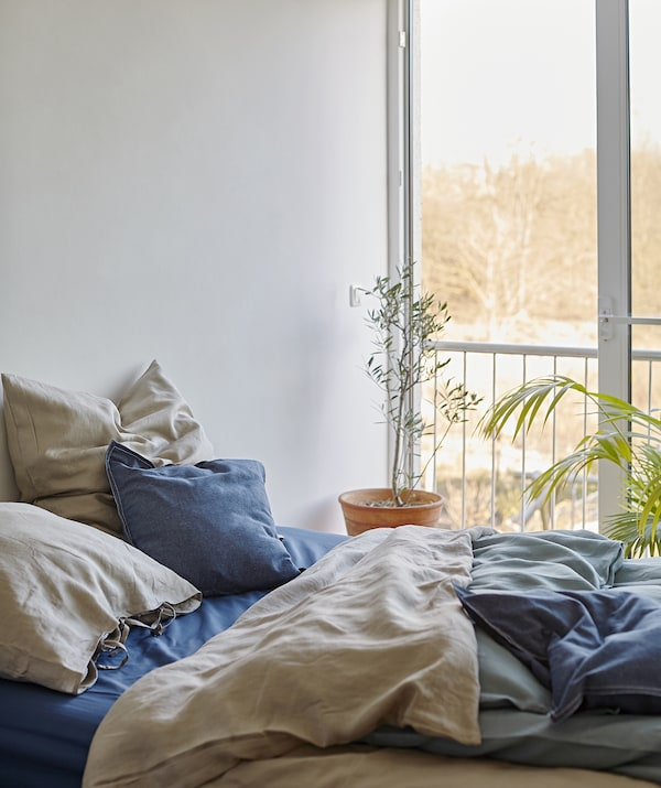 A bed with layered bedding in blue and beige next to a large window.