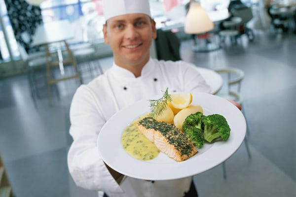 A chef holding a dinner plate with a salmon entree.