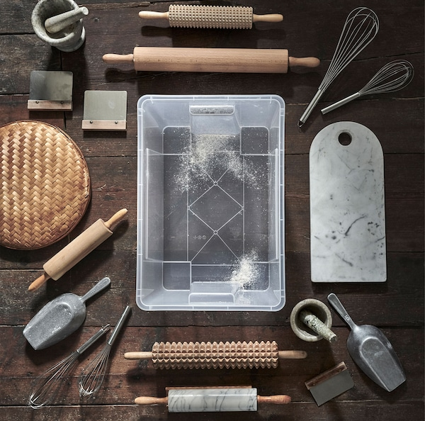 A clear SAMLA container placed on a wooden floor, surrounded by various baking supplies.