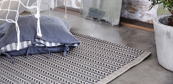 Blue pillow sitting on a grey and black woven outdoor rug