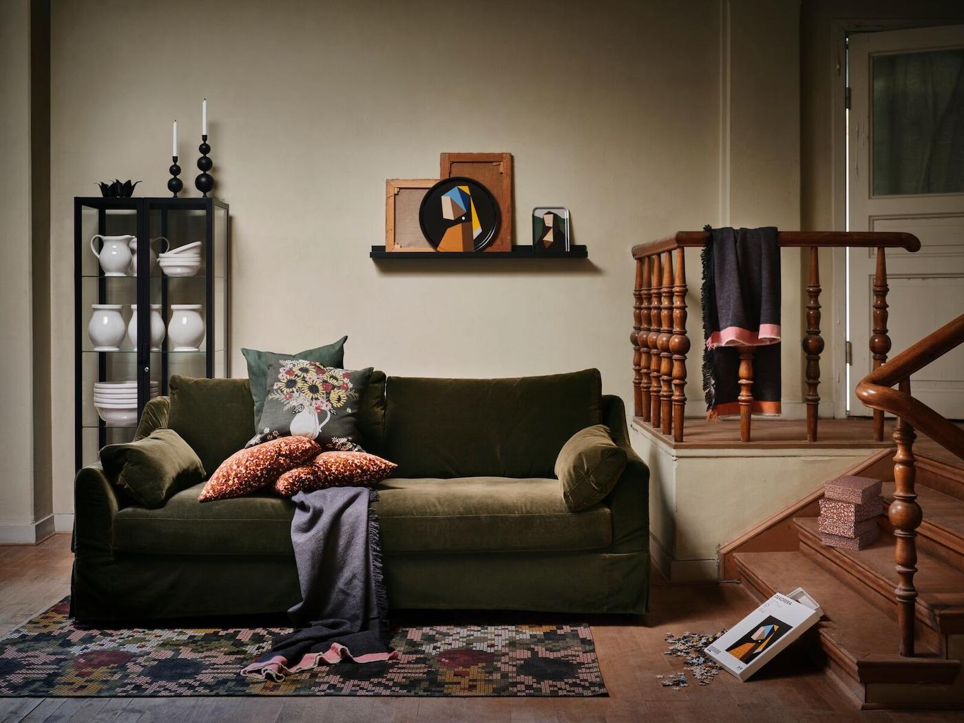 Verschillende artikelen uit de DEKORERA collectie van IKEA staan in een warme woonkamer, met een donkergroene zitbank en wat kussens.