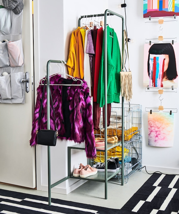 Corner of a room dedicated to a small, openly stored wardrobe, hung on a clothes rack and folded in metal-wire crates.