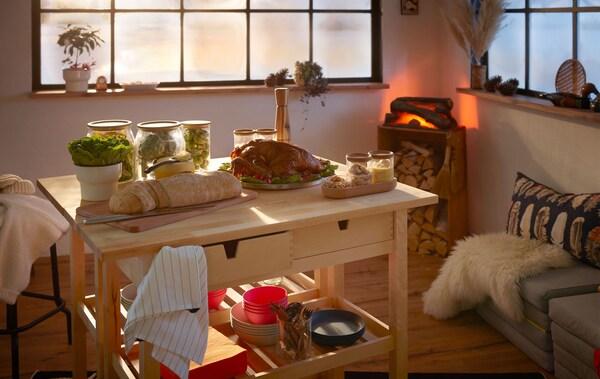 Interior estilo cabana de madeira, com um bufê pequeno, mas festivo, disposto em dois carrinhos de cozinha; lareira falsa no canto.