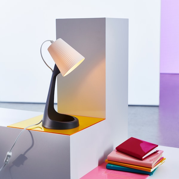 A SVALLET work lamp with a sleek design with a dark grey lamp base and a white lamp shade.