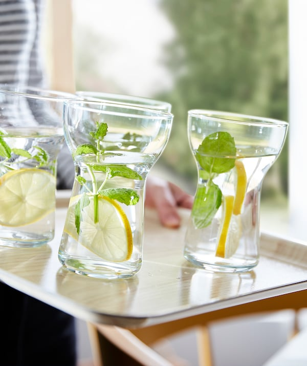 Easy-to-grip OMTÄNKSAM glasses filled with water, lemon slices and green sprigs, standing on an anti-slip tray.