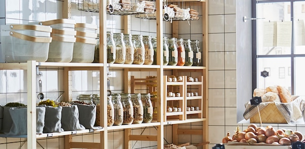 wood pantry shelving unit in a kitchen with white subway tiles.