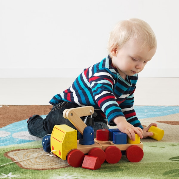 A toddler is playing with a red, blue and yellow IKEA MULA wooden crane with blocks on a green and blue children's rug.