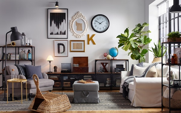 Estanterías de madera y metal FJÄLLBO de estilo industrial en un salón con asientos mullidos, plantas y una galería mural.
