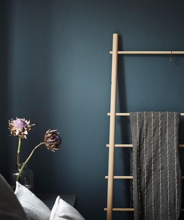 Échelle porte-serviettes en bois appuyée contre un mur foncé, dans une chambre.