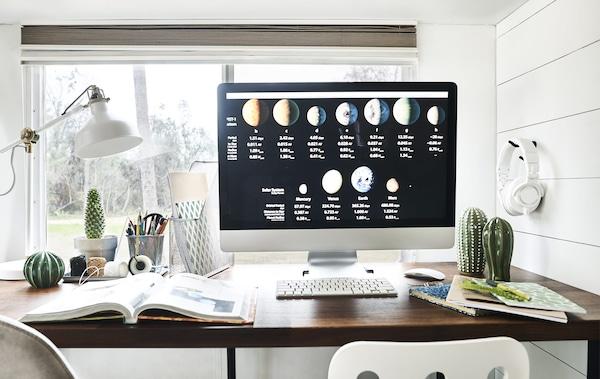 Écran d'ordinateur sur un bureau, avec cahiers, classeurs et une lampe.