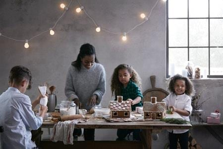 A woman with three kids decorating gingerbread houses.