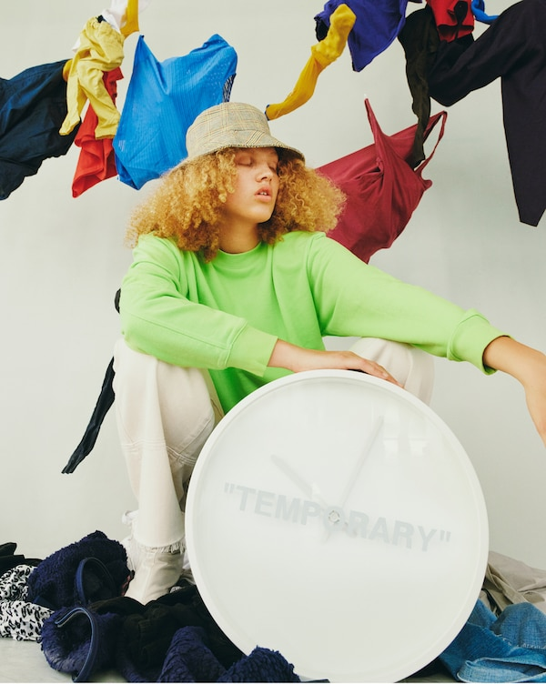 "A white clock with the word ""TEMPORARY"" written on its face in front of a sitting model."