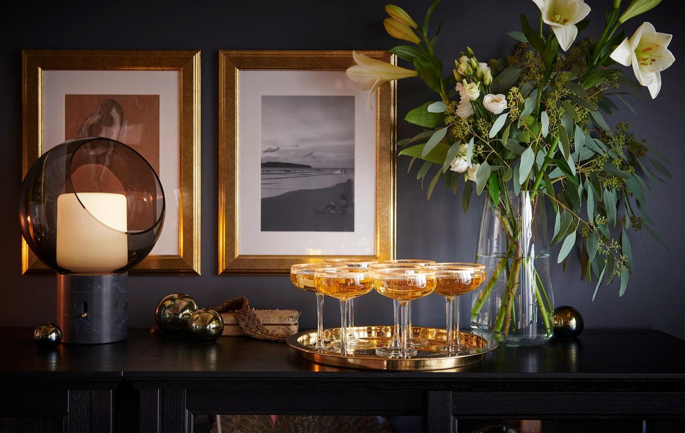 Edle Champagner-Gläser stehen auf einem Tablett auf einer dunklen, stilvollen Vitrine mit Blumen.
