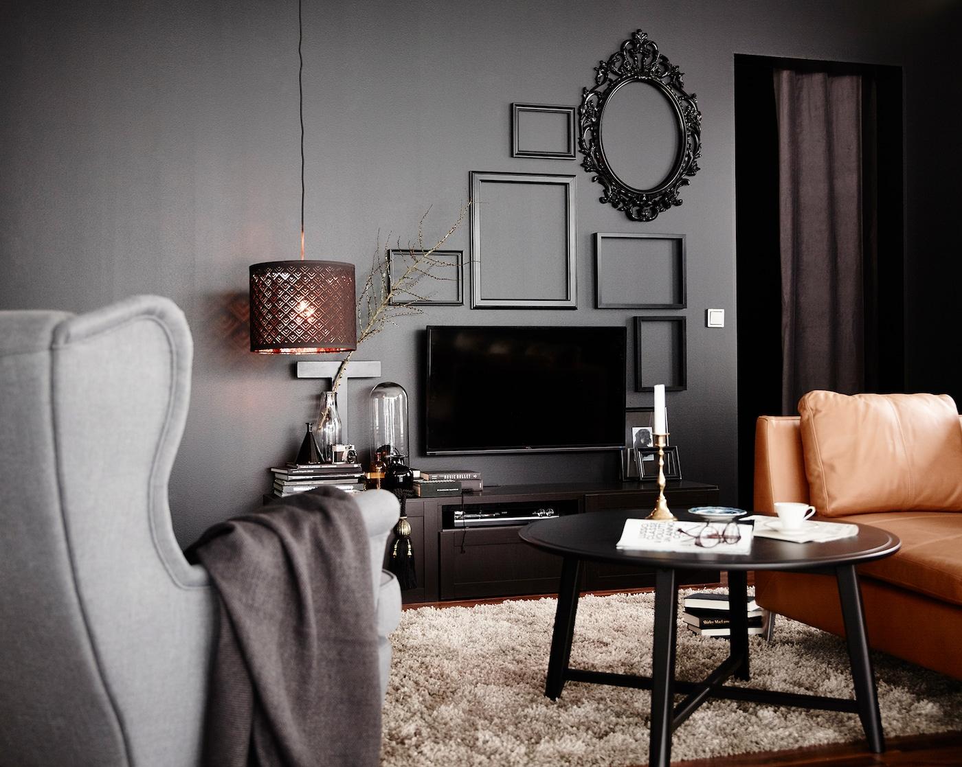 Edles Wohnzimmer mit einer TV-Wand & Bilderrahmen, Sessel, Sofa und Tisch.