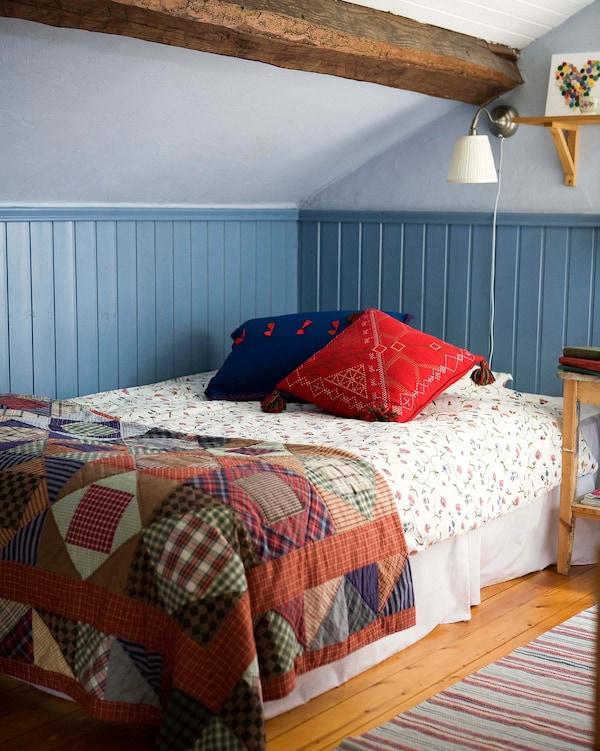 Edredón a los pies de la cama en un dormitorio azul y blanco.