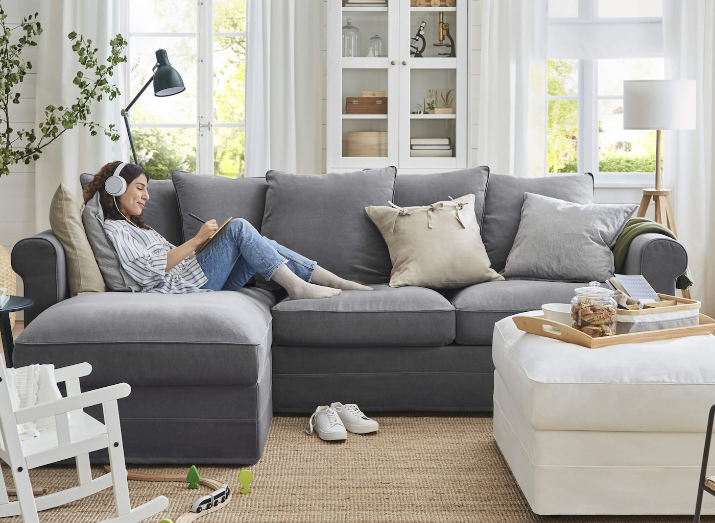 A woman with headphones lounging on a gray sofa with a chaise lounge in a living room with tall windows.