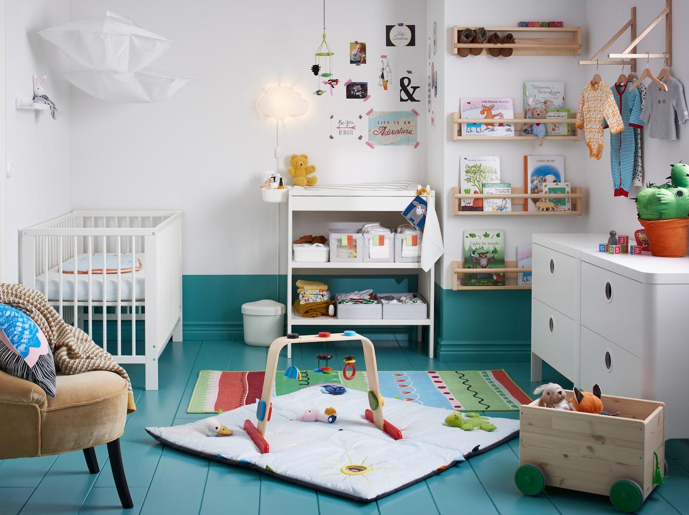 Een babykamer met ledikant, commode, ladekast en speelgoed.