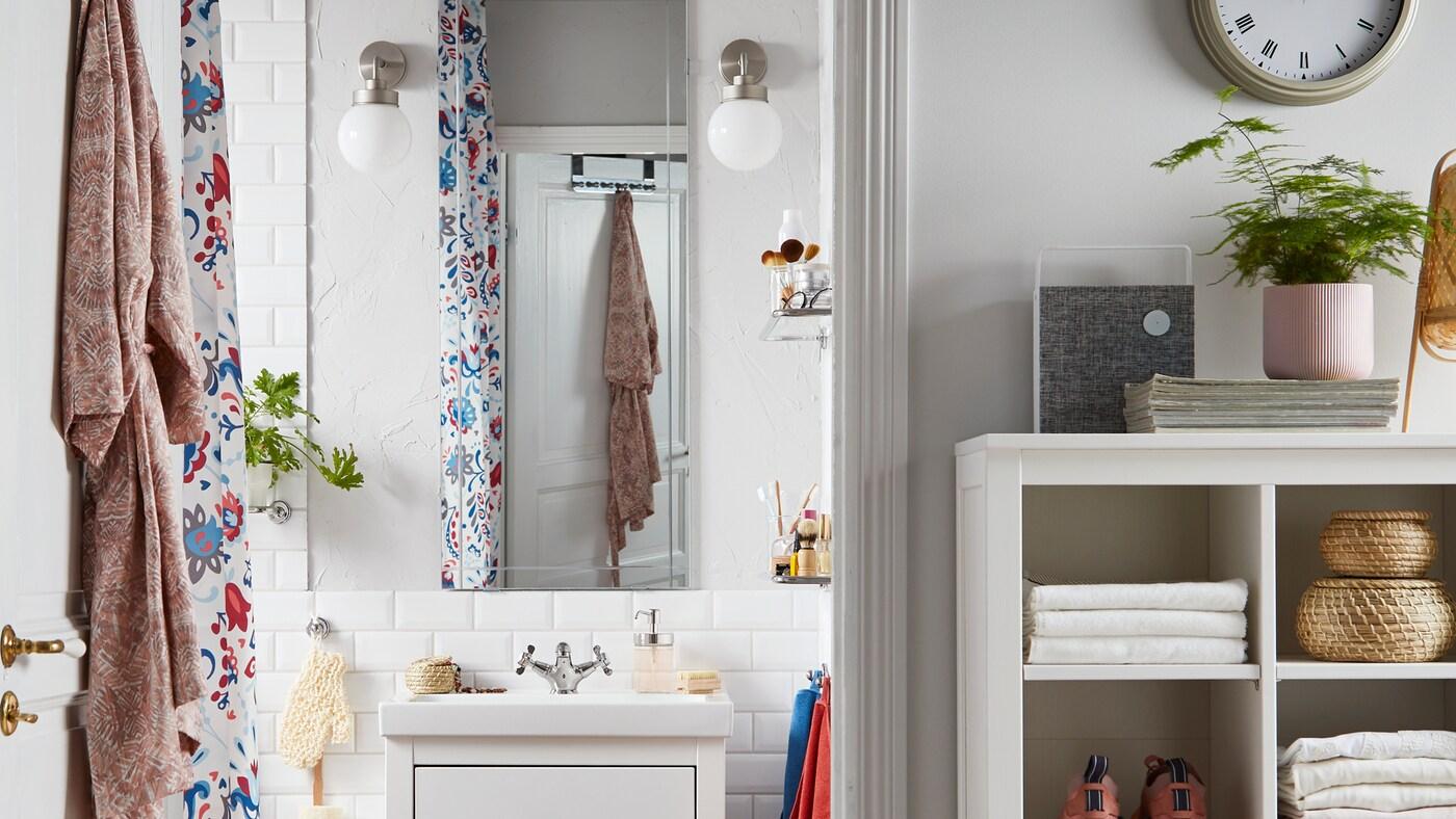 Een badkamer met een EIDSÅ spiegel, twee witte FRIHULT wandlampen, een opbergmeubel met handdoeken, sneakers en rotanmanden.