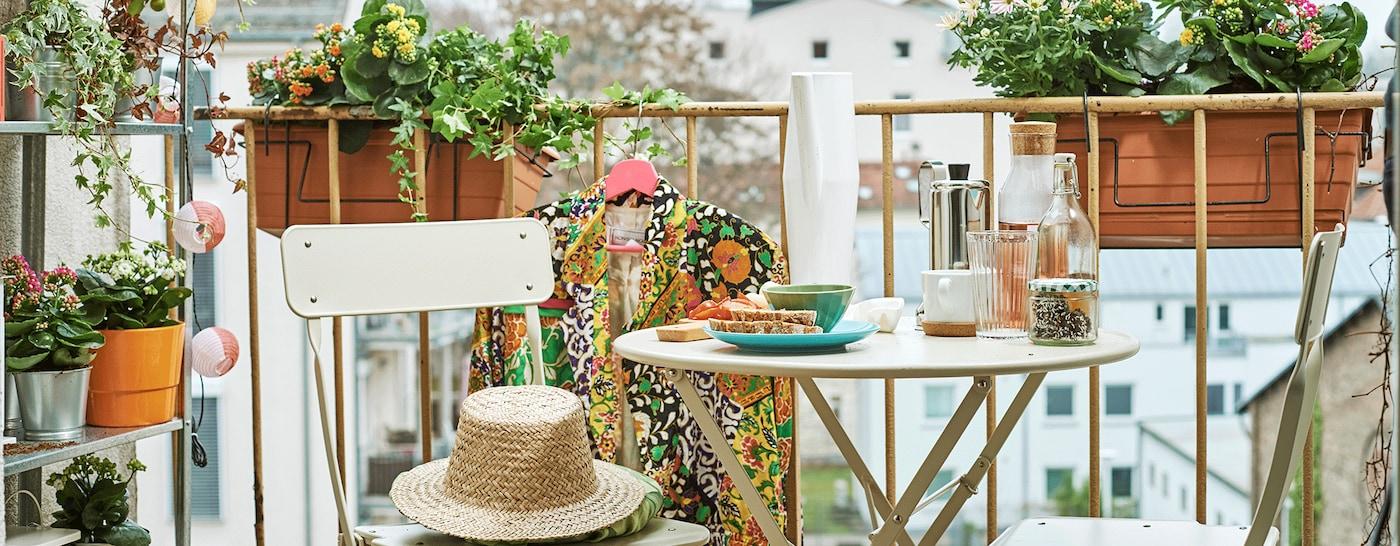 Een balkon in de stad met bloembakken, een open kast met planten, een lichtsnoer en een eetset in bistrostijl, vol met lekkere hapjes.