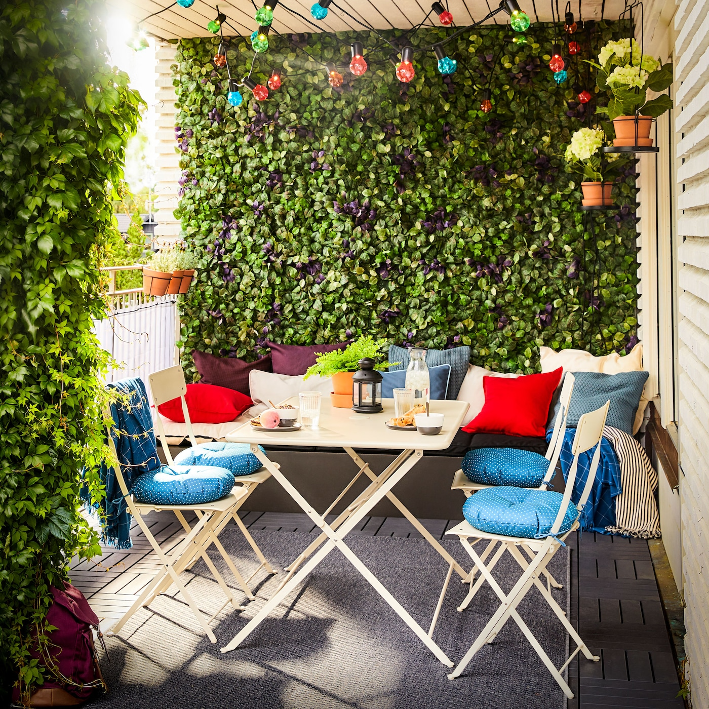 Een balkon met SALTHOLMEN tafel en vier beige stoelen. Felgekleurde kussens en lichtslingers geven een levendig tintje.