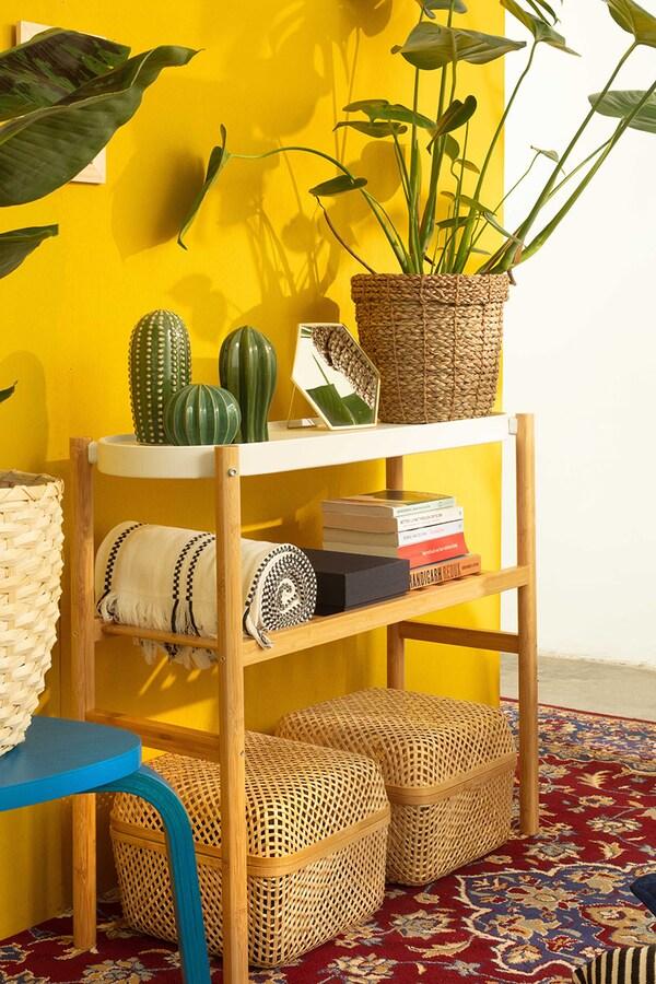 Een bamboe plantenstandaard met een plant en snuisterijen tegen een gele muur