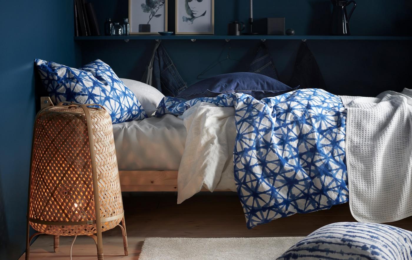 Een bed aangekleed met beddengoed met motief en een staande lamp van bamboe in een kamer met donkerblauwe muren.