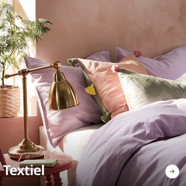 Een bed dat opgemaakt is met een lila kleurig dekbedovertrek, wat sierkussens en een goudenlamp staat naast het bed op een nachtkastje.