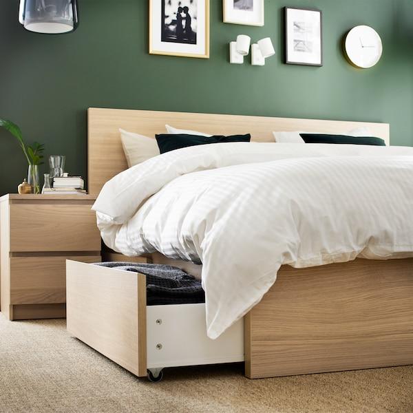 Een bedframe en nachttafeltje in wit gebeitst eiken fineer en dekbedovertrek en kussenslopen in wit.