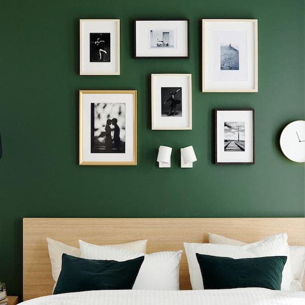 Een bedframe in wit gebeitst eiken fineer, dekbedovertrek en kussenslopen in wit en goudkleurige fotolijsten.