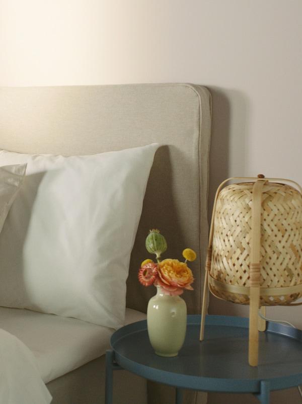 Een beige gestoffeerd bed met wit beddengoed erop, met een ronde blauwe tafel ernaast waarop een rotan tafellamp staat.