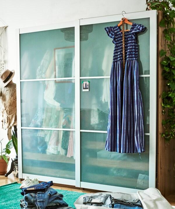 Een blauwe jurk hangt voor een kleerkast met schuifdeuren. Ernaast staat een paspop, ervoor ligt een stapel jeans.