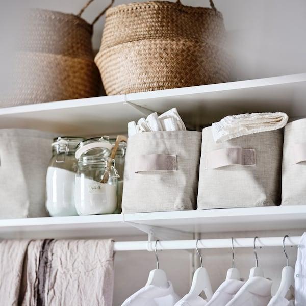 Een BOAXEL systeem met witte planken en daarop PURPLINGA opbergdozen en glazen potten met waspoeder erin.