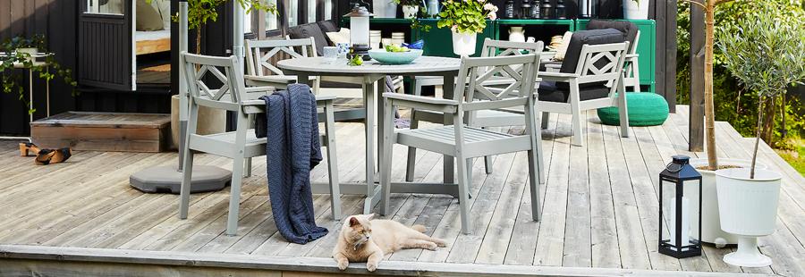 Een buitenruimte op een houten terras met een beige parasol, grijze buitenmeubelen, groene bomen in potten en een rosse kat.